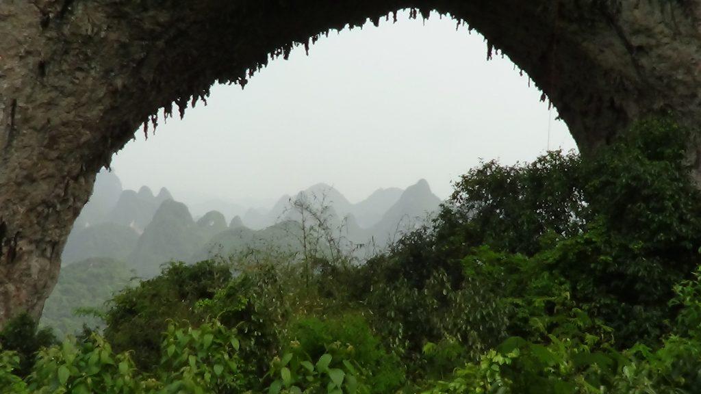 Looking through Moon Rock, near Yangshuo, to Karst Peaks beyond.